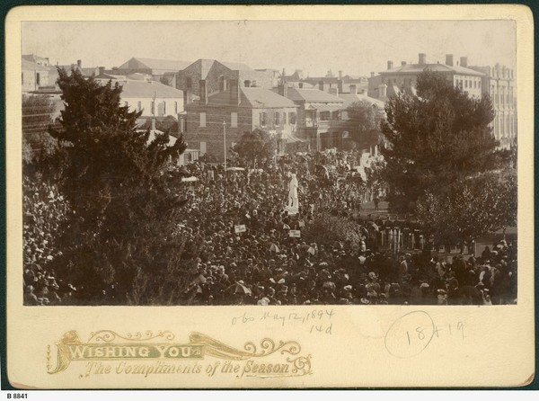 Image: crowds surrounding stone statue of standing man