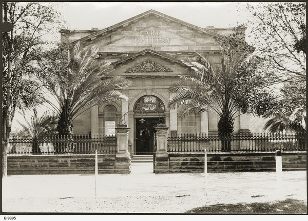 """Image: Black and white photograph of the front of a building. Palm trees stand on either side of the front of the building. The building reads """"ART GALLERY"""""""