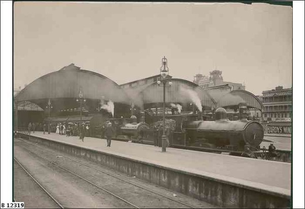Image: a steam train is stopped beside a platform on which stands a number of men and women in early 20th century clothing. Its carriages stretch away into the distance and pass under a curved roof platform cover.