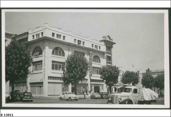 Image: a four storey white stucco building with large arched on its third floor. It sits on the corner of a tree lined street which is busy with 1950s era automobiles.
