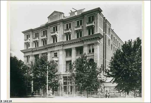 Image: a five storey stone building with a symmetrical façade under construction. There are balconies and balconets on most floors although they are of different shapes and formations, some protruding and some set into the building.