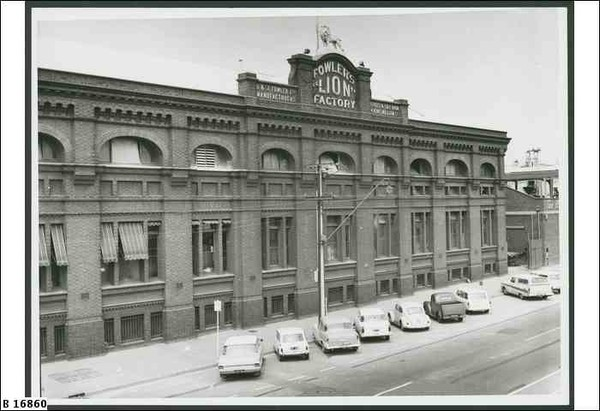 "Image: 1960s cars are parked outside a large, three storey brick factory building. Some of the windows bear striped awnings and there is a parapet sign reading ""Fowlers Lion Factory"" which is topped with a life-sized lion statue"
