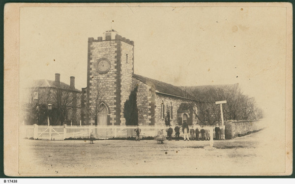 Image: A low, squat church building stands at the intersection of two dirt roads. A man stands in front of the fence bordering the churchyard
