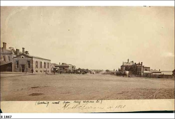 Image: a wide dirt road with a scattering of one to three storey stone and brick buildings. Parked outside one of the buildings is a line of horse drawn vehicles for hire.