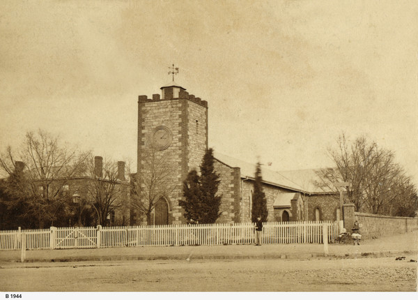 Image: A low, squat church building stands at the intersection of two dirt roads. Two people stand in front of the church