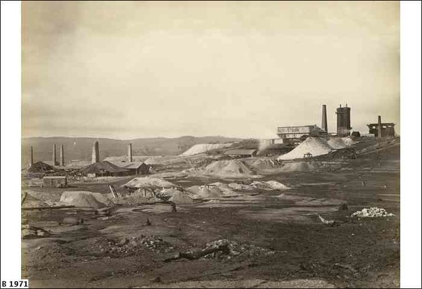 Image: Several large chimneys and buildings are arrayed among numerous tailings piles. A low mountain range is visible in the background