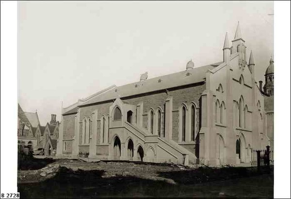 Image: a side view of a stone church with simple facade including three short spires placed centrally at one end of the building. A large staircase runs up the side of the church providing access to a second storey entrance.