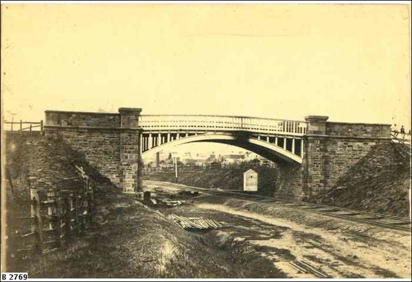 Image: a metal arched bridge with stone abutments passes over a railway track.