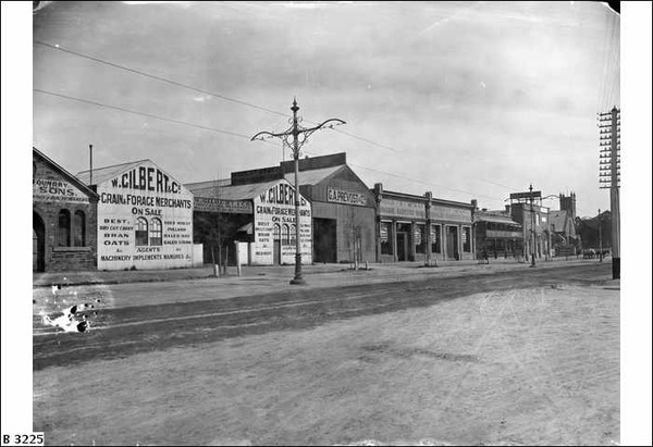 Image: a series of small single storey industrial buildings lining a wide dirt road. Many of the buildings feature painting signs advertising the products sold inside.