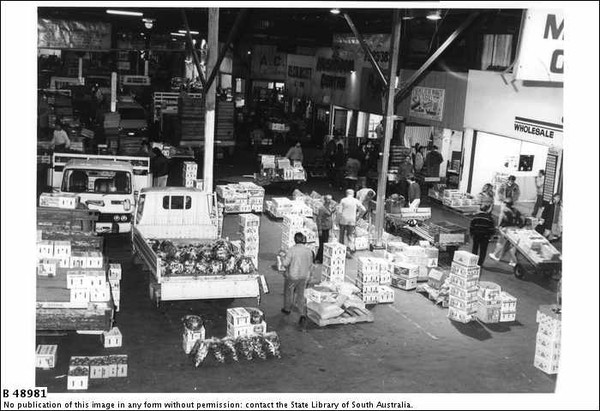 Image: men and women unload boxes of fruit and vegetables from 1980s era trucks in a covered market with shops lining one wall