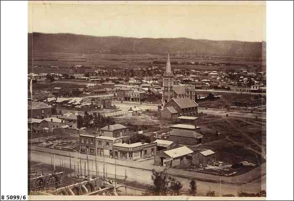 Image: A church with large steeple surrounded by houses, buildings and a few dirt streets