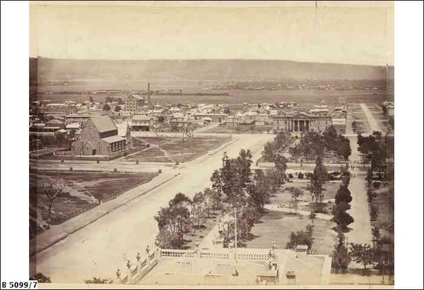 Image: A wide dirt avenue bordered by a park on one side and church with surrounding paddock on the other. Large hills are visible in the background