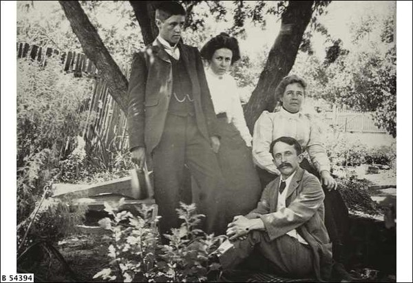 Image: A moustachioed man in a suit sits on a rug. Leaning against a tree behind him are a young man, young woman, and and adult woman in Edwardian attire