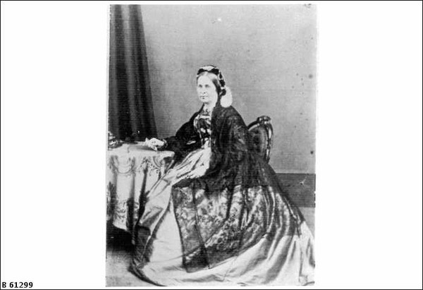 Image: Black and white picture of seated woman in three quarter profile wearing a long dress.