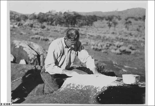 Image: A young Caucasian man in a shirt and jeans uses Aboriginal techniques to create art on a rock in a remote location