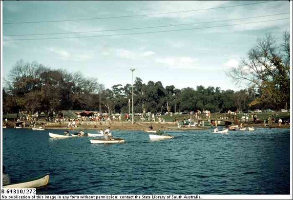 Image: Men and women row boats on an artificial lake set in the middle of a park while a large crowd watches from the shore.