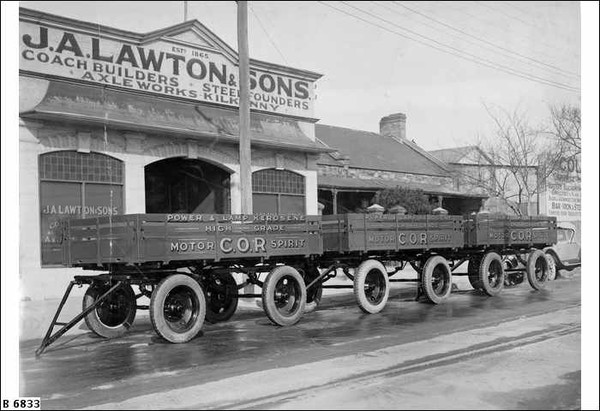 """Image: three four wheeled trailers are parked in a row outside of a single storey building with arched windows and open entranceway. A parapet sign on the building reads: """"J.A. Lawton & Sons. Coach builders, Steelfounders, Axelworks, Kilkenny"""""""