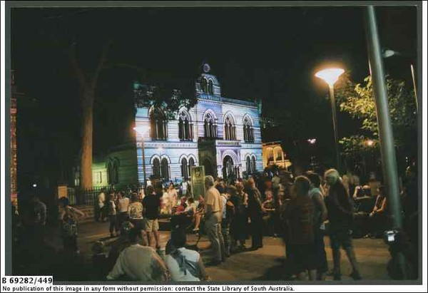 Image: a crowd gathers in front of a gothic style building which is lit up by a projection and glows purple and green