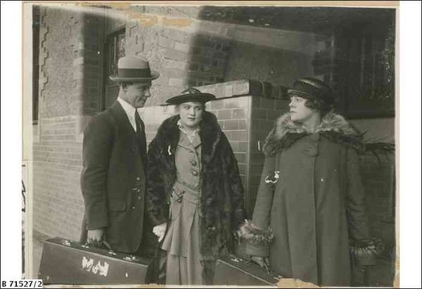 Image: A theatrical still of a young woman looking with disapproval at a young couple. The group is posed together outside the front porch of a smart house of the Art Deco period