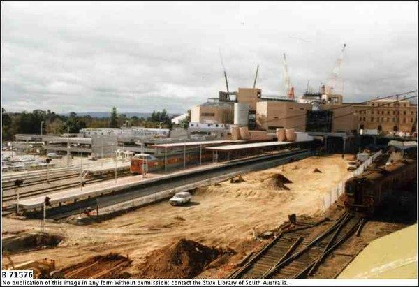 Image: a 1980s era diesel train is stopped at a platform amidst a large construction site. Behind it cranes work on a new building.
