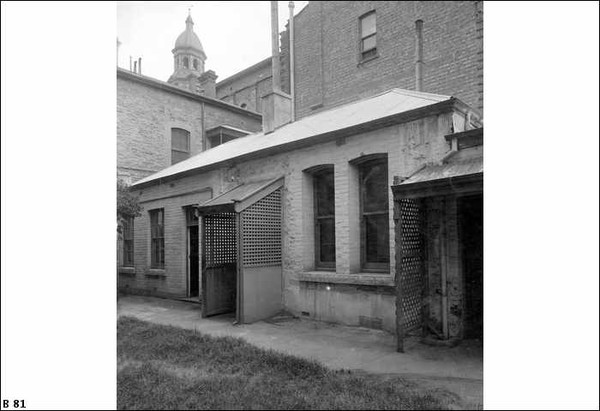 Image: A low, rectangular stone and brick building surrounded on three sides by much taller brick and stone buildings. The back door of the building features a wooden latticework awning