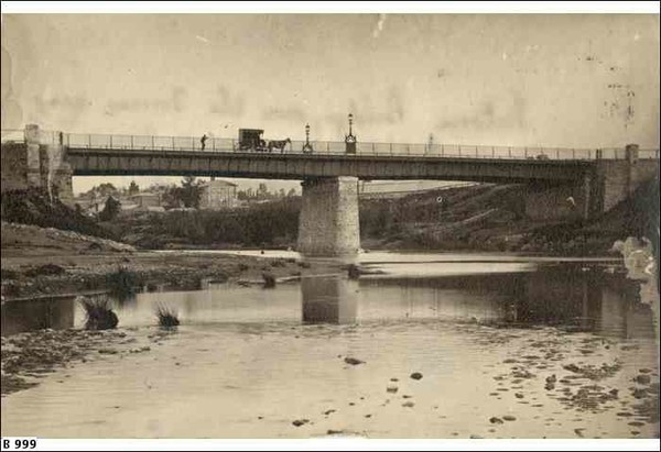 Image: a metal bridge with stone abutments and central pylon passes over a shallow river.