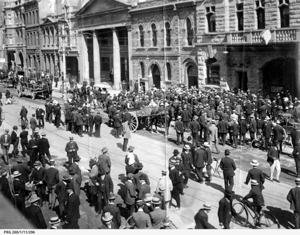 Image: A large group of men stand in the street looking towards the front of a building.