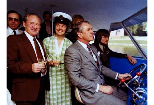 Image: a man in a grey suit sits at a wheel steering a small boat. Behind him other men and a woman in a green dress and captain's hat hold champagne and smile at the camera.