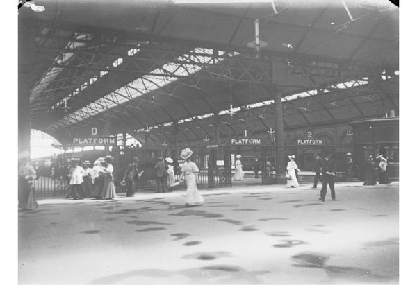 Image: the interior of a railway station with at least three platforms visible. The curved roof features skylights and is supported by metal beams. In the foreground are a number of men and women in early 20th century clothing.