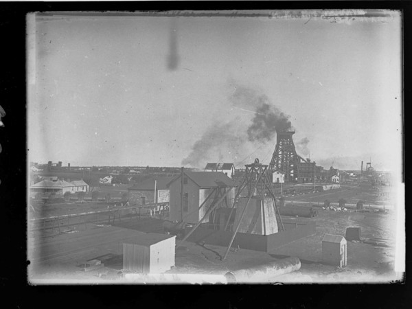 Image: Smoke billows from a steel tower surrounded by a number of buildings and an array of industrial equipment