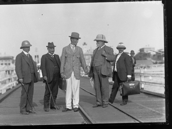 A man in a suit and hat is greeted by other men on a jetty. A coastal town is visible in the background