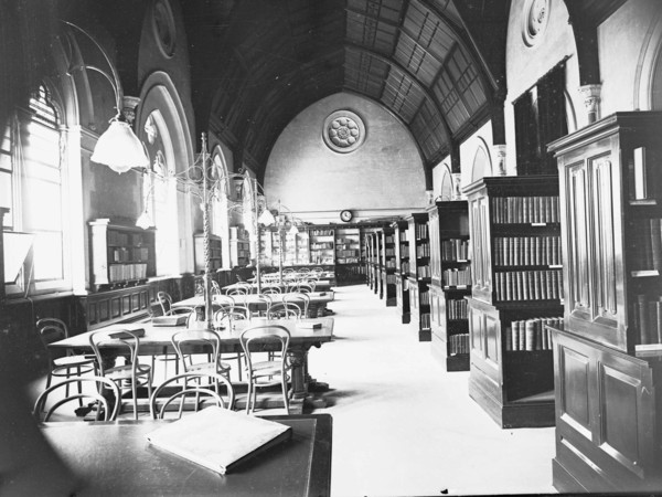 Image: A long, well-lit room containing several shelves of books on one side and six reading tables on the other