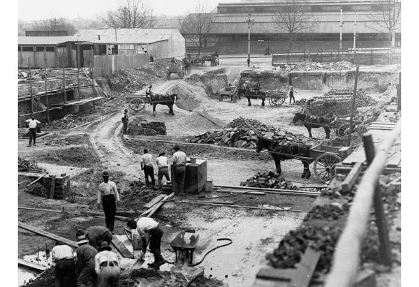 Image: a large demolition site with piles of rubble. The site is dotted with men in early 20th century clothing and horse drawn carts.