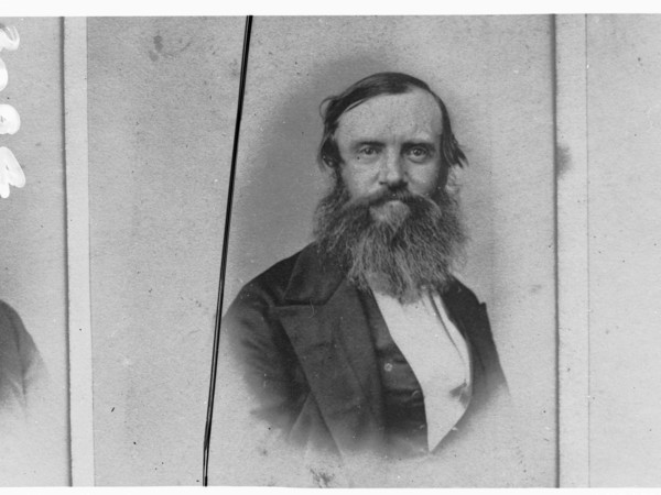 Image: A middle-aged man with a long, unkempt beard and dressed in mid-nineteenth century attire poses for a photograph