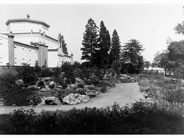 Image: An ornate conservatory building sits within a densely planted garden in full bloom with a winding gravel path in the foreground.
