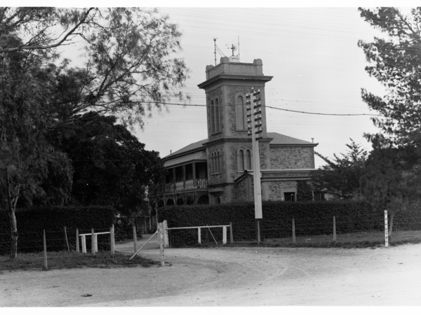 Image : Old stone building with tower and dirt driveway.
