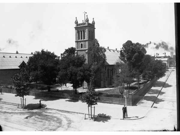 Image: A large, stone church surrounded by trees stands on the corner formed by two streets. A man in a brimmed hat stands in front of the churchyard