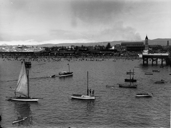 Image: View of boats in the water with crowds of people on the beach in the background