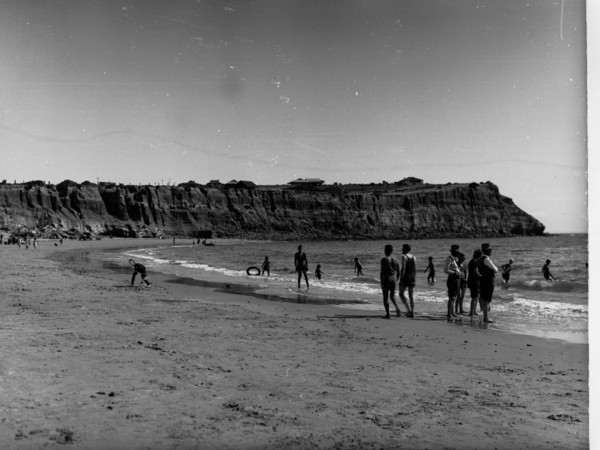 Image: Beach scene with people playing on the sand and in the water with rugged cliffs in the background