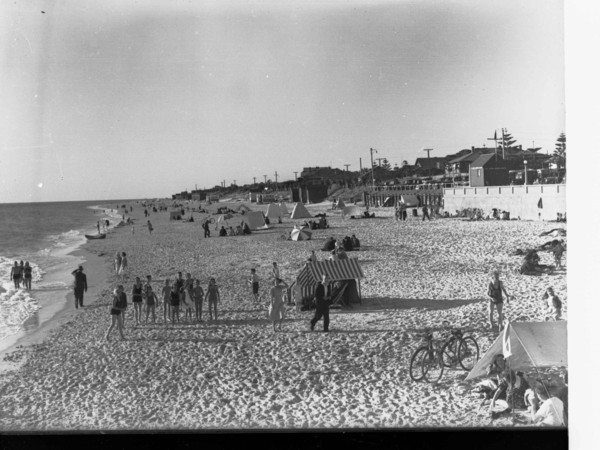 Image: People on a beach in swimsuits and sheltering from the sun under tents.