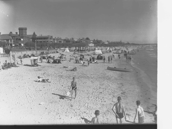 Image: People sunbathing and walking on a beach
