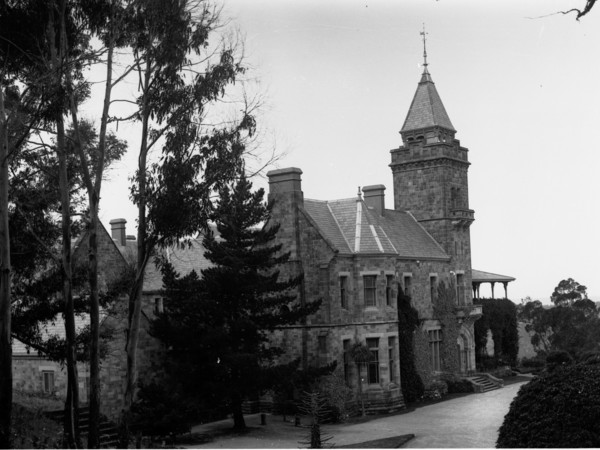Image: A large, two-storey brick and stone building with a central tower
