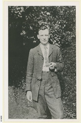 Bespectacled man in two piece suit and tie holding a pipe, and standing in a garden