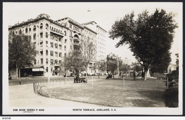 Image: Black and white photograph taken from across North Terrace looking West, with the Liberal Union Club in the distance. The photograph was taken in the 1950s and shows people sitting on park benches looking towards the Liberal Union Club building.