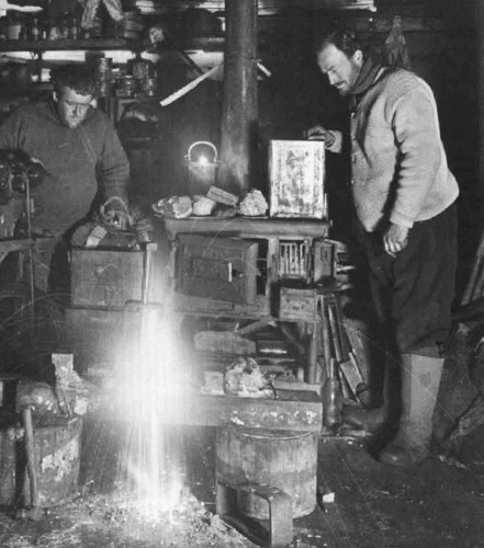 Image: Two men stand in a darkened room next to a pot-bellied stove. One observes the other as he welds a metal vise