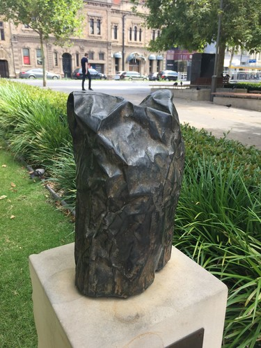 Crumpled bronze bag on plinth with grass and plants nearby
