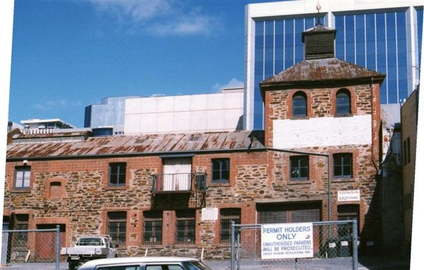 Image: Colour photograph of an historic bluestone building with red brick quoins and detailing surrounded by sky scrapers and fronted by a carpark