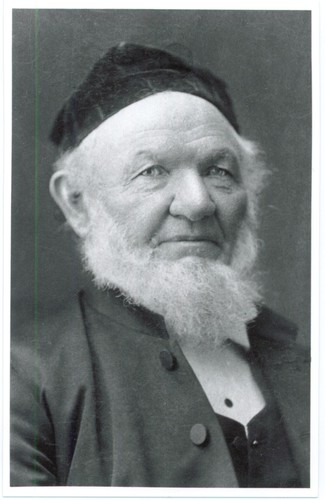Image: a head and shoulders portrait of a man with a bushy white beard wearing a dark velvet cap.
