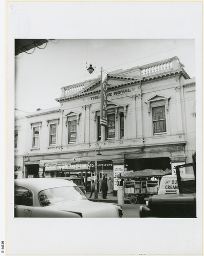 Image: Front view of a theatre building with cars driving in the foreground and people on the street