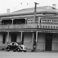 Image: a two storey corner hotel with balcony. A 1940s era car is parked outside. Signs on the upper level advertise West End Exhibition Stout and Seppelts wine.